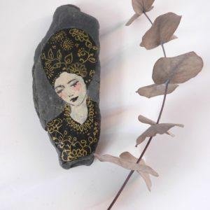 Galet peint femme en noir et or